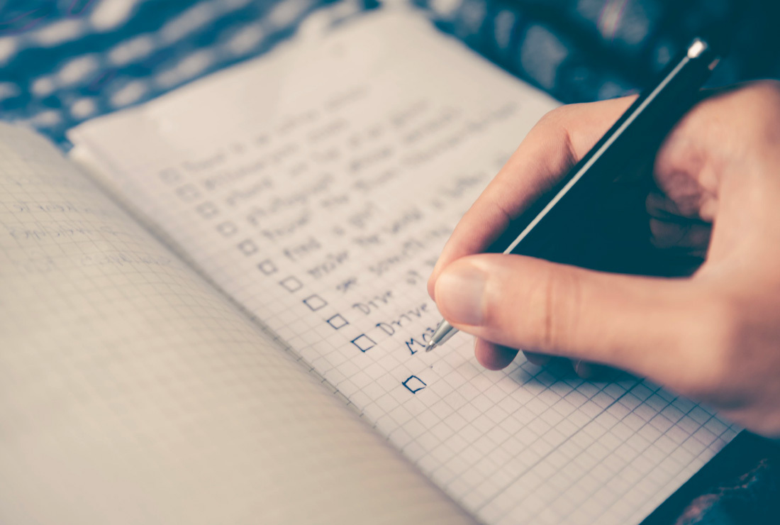 Hand writing a conference planning checklist on paper