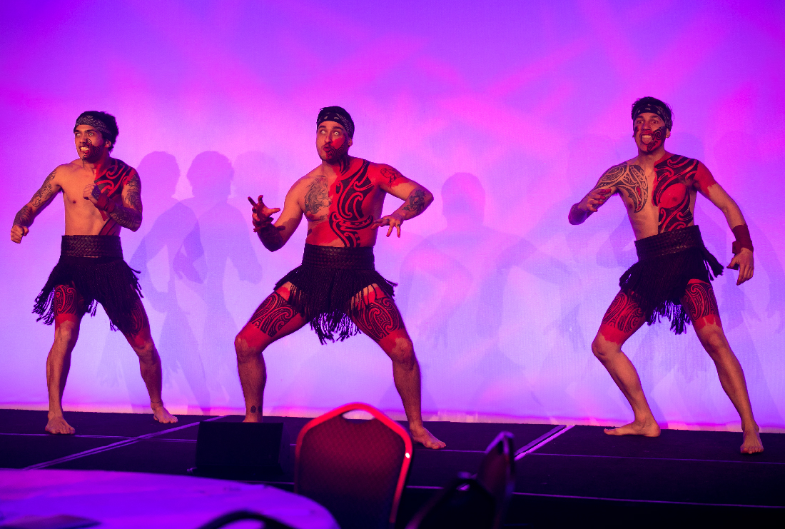 Performers at a corporate event with purple background lighting