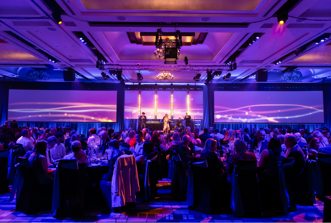 Ballroom with corporate event. Tables and people, all lit up in purple.